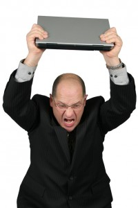 business man with laptop over head - mad